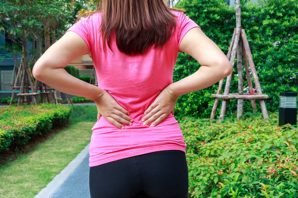 Woman wtih back pain while gardening in Long Beach.