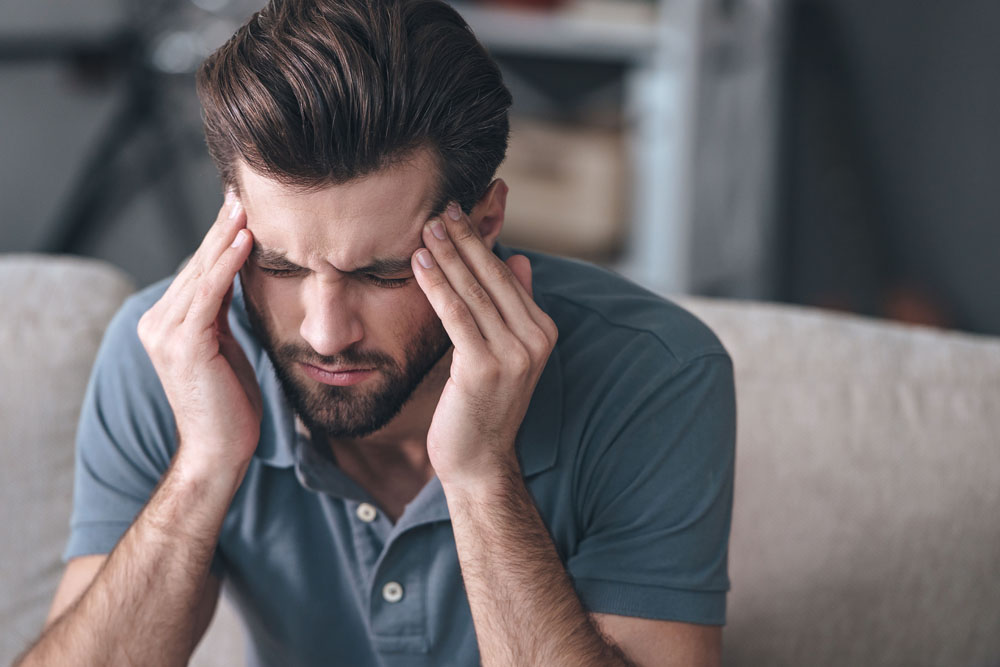 Man with a headache needs chiropractic care.